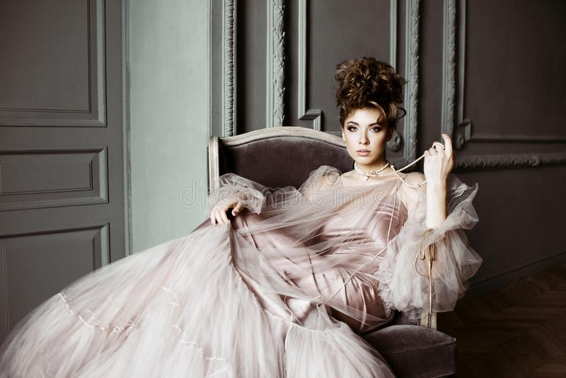 Fashionable female portrait of cute lady in pink dress indoors royalty free stock photos