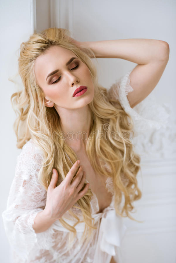 Fashionable female portrait of cute lady in white robe indoors. Close up beautiful model girl in elegant pose. Closeup beauty blonde woman with hairstyle and stock image