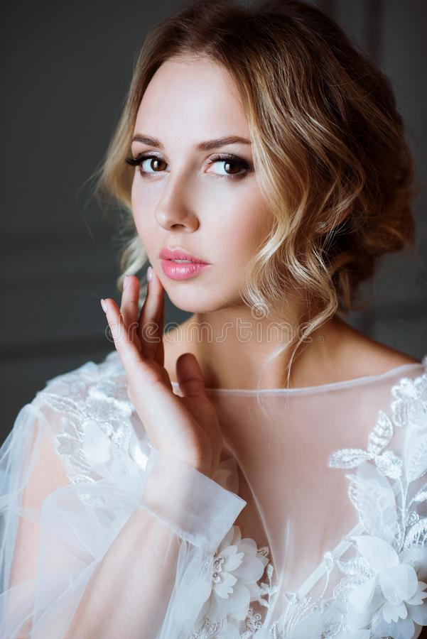 Fashionable female portrait of cute lady in white robe indoors royalty free stock photo
