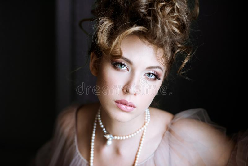 Fashionable female portrait of elegant lady with jewelry indoors. Close up beautiful model girl. Closeup beauty blonde woman with hairstyle, makeup and royalty free stock photography