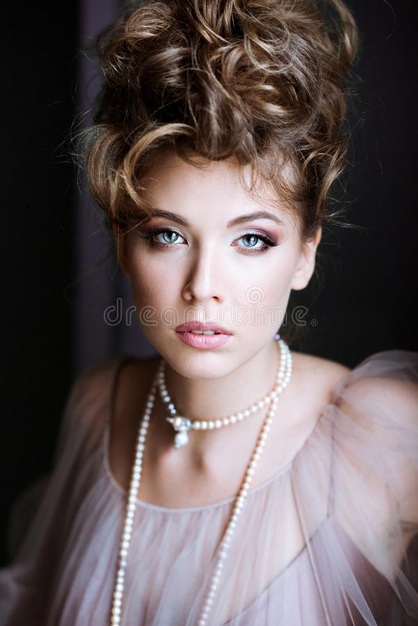 Fashionable female portrait of elegant lady with jewelry indoors. Close up beautiful model girl. Closeup beauty blonde woman with hairstyle, makeup and royalty free stock photo