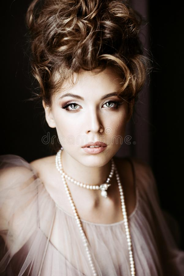 Fashionable female portrait of elegant lady with jewelry indoors. Close up beautiful model girl. Closeup beauty blonde woman with hairstyle, makeup and stock photography