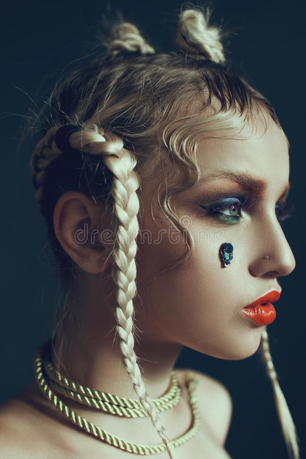 Fashionable female portrait in studio with hair, make-up and flowers. Fashionable and beautiful female portrait in the studio with hair, make-up, bare shoulders royalty free stock photo