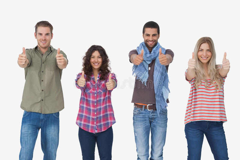 Fashionable friends looking at camera and giving thumbs up. On white background stock photography