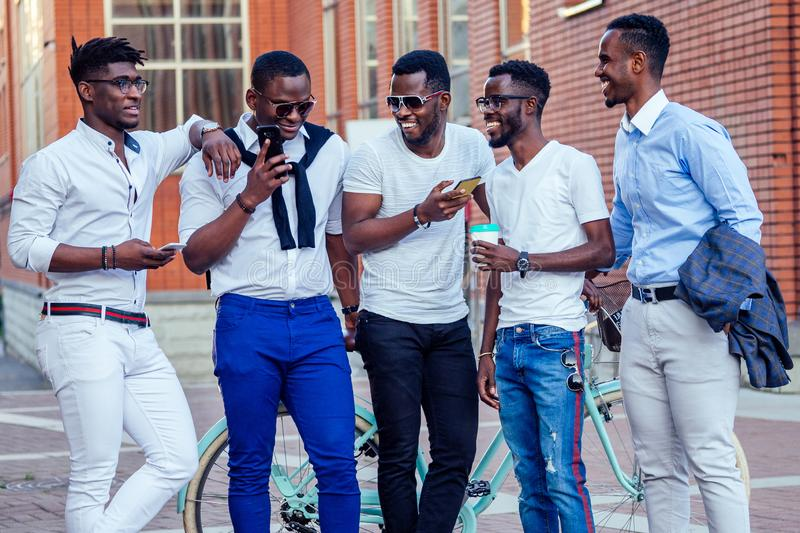 Fashionable friends at a meeting. a group of five handsome African American men well-dressed businessmen having fun and royalty free stock images