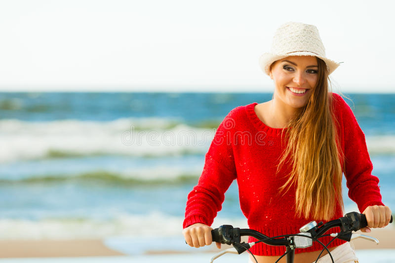 Fashionable girl with bike outdoor. Young active girl with bicycle on seaside. Smiling cute woman resting near to sea in summer. Fashionable tourist on fresh royalty free stock image