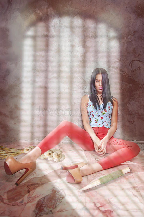Fashionable girl in bright clothes siting. Shadow of the lattice. vampire style. Photo in studio of woman in bright clothes, shadow of the lattice. vampire style royalty free stock photo