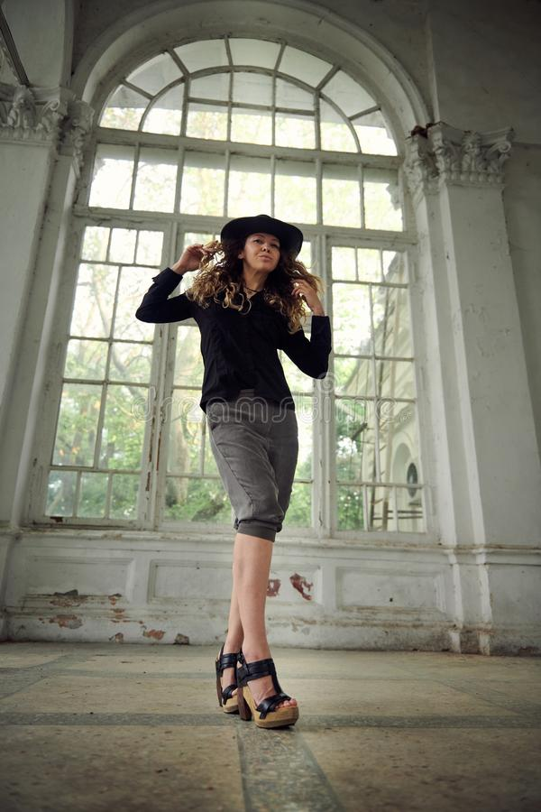 Fashionable girl dressed in black shirt, hat and wide trousers posing near old white house stock image