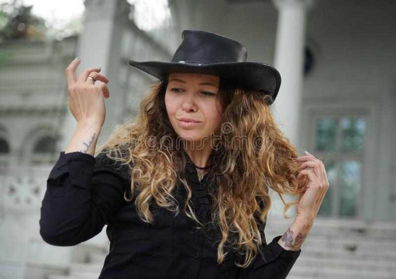 Fashionable girl dressed in black shirt, hat and wide trousers posing near old white house royalty free stock photo