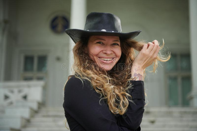 Fashionable girl dressed in black shirt, hat and wide trousers posing near old white house stock photos