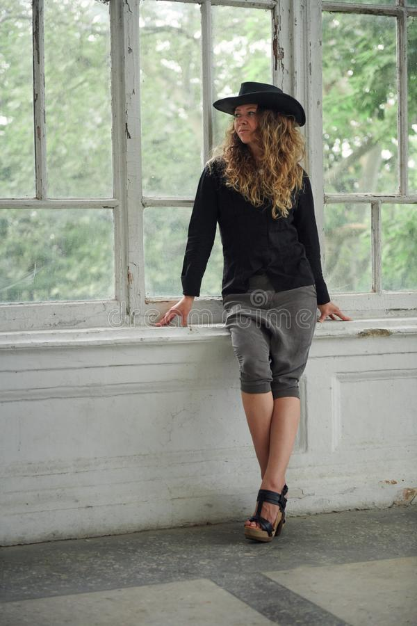 Fashionable girl dressed in black shirt, hat and wide trousers posing near old white house royalty free stock photos