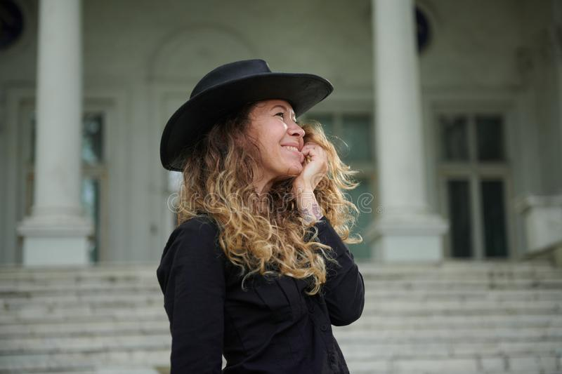 Fashionable girl dressed in black shirt, hat and wide trousers posing near old white house stock images