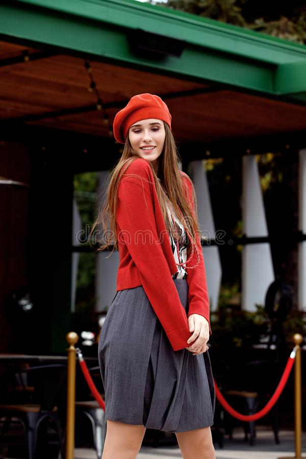 Fashionable girl dressed in a gray skirt, a red blouse on the t-shirt and red beret poses in the street on the sunny day stock photo