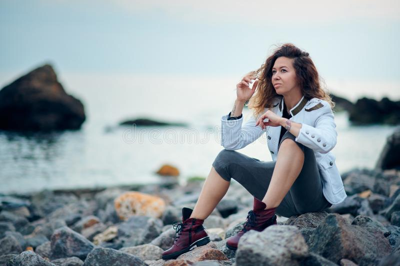 Fashionable girl dressed in white jacket and wide trousers posing near sea in the evening stock photos