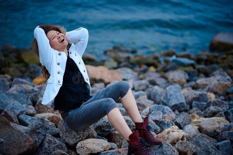 Fashionable girl dressed in white jacket and wide trousers posing near sea in the evening royalty free stock photos