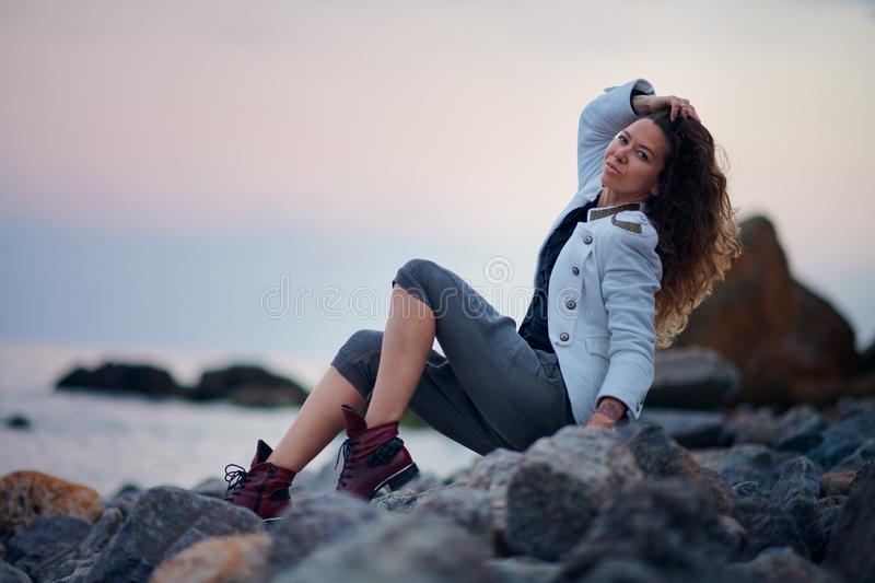 Fashionable girl dressed in white jacket and wide trousers posing near sea in the evening stock photo