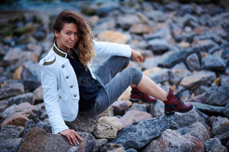 Fashionable girl dressed in white jacket and wide trousers posing near sea in the evening royalty free stock images