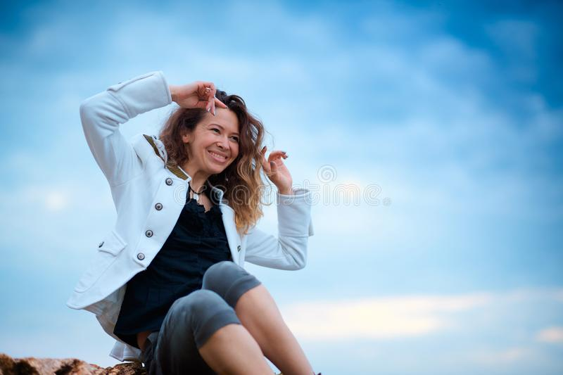 Fashionable girl dressed in white jacket and wide trousers posing at sunset sky background, sits on the stone royalty free stock photo