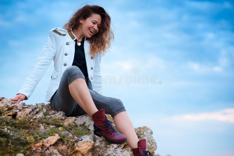 Fashionable girl dressed in white jacket and wide trousers posing at sunset sky background, sits on the stone stock photos