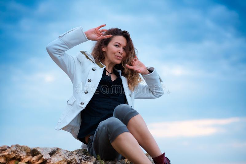 Fashionable girl dressed in white jacket and wide trousers posing at sunset sky background, sits on the stone stock images