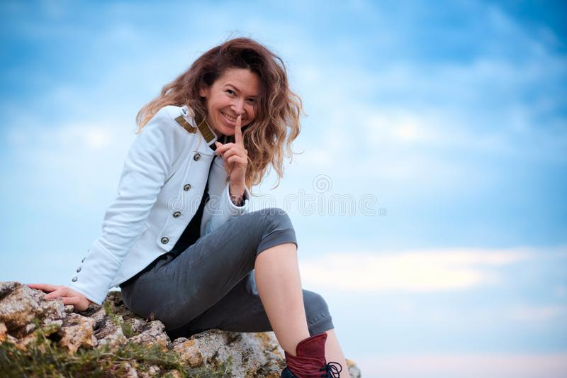 Fashionable girl dressed in white jacket and wide trousers posing at sunset sky background, sits on the stone royalty free stock images