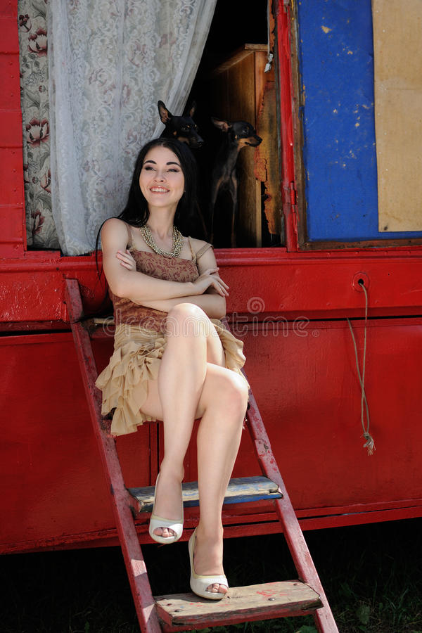 Fashionable girl guarded by two toy terrier dogs. circus trailer. Fashionable girl guarded by two toy terrier dogs. Behind the scenes of the circus. On stock photography