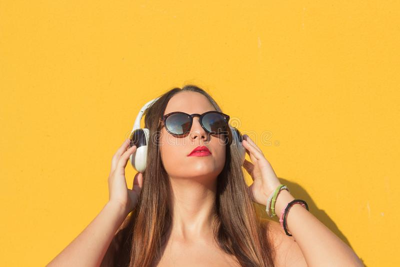Listening music in her headphones with yellow background stock images