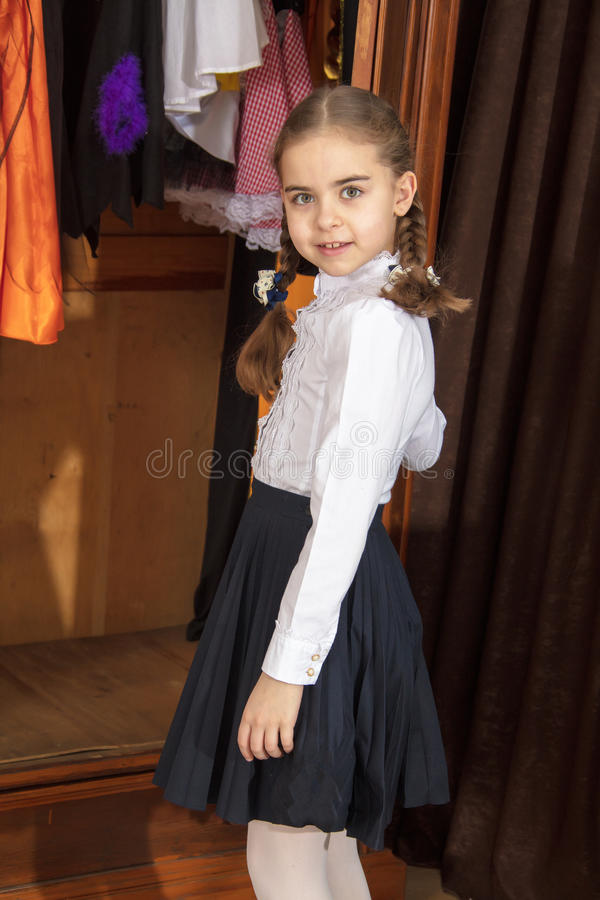 The fashionable girl opens the wardrobe. Beautiful little schoolgirl girl with braided braids on her head, in a white blouse and black skirt. She opens the royalty free stock images