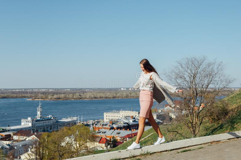 Fashionable girl is on the parapet, balancing stock photo