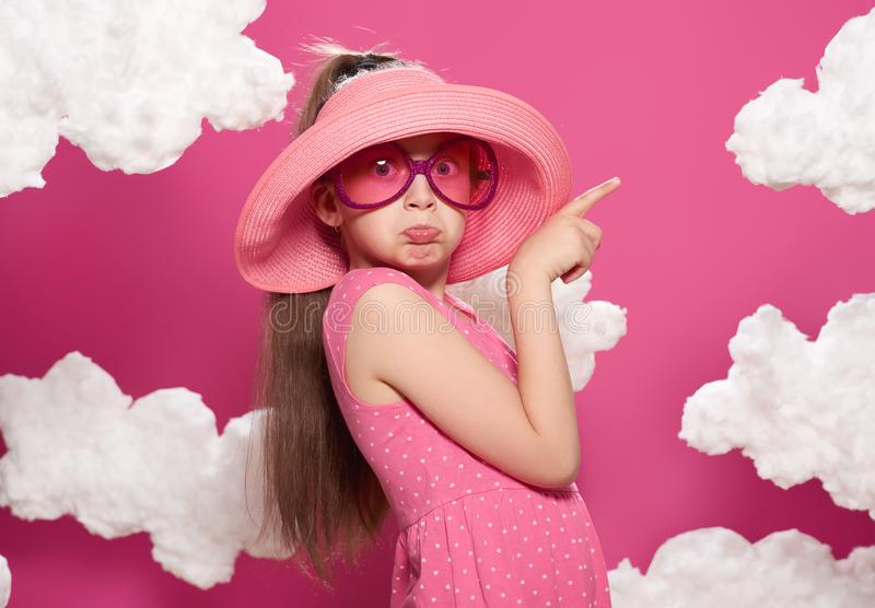 Fashionable girl posing on a pink background of clouds, pink dress and hat stock photo