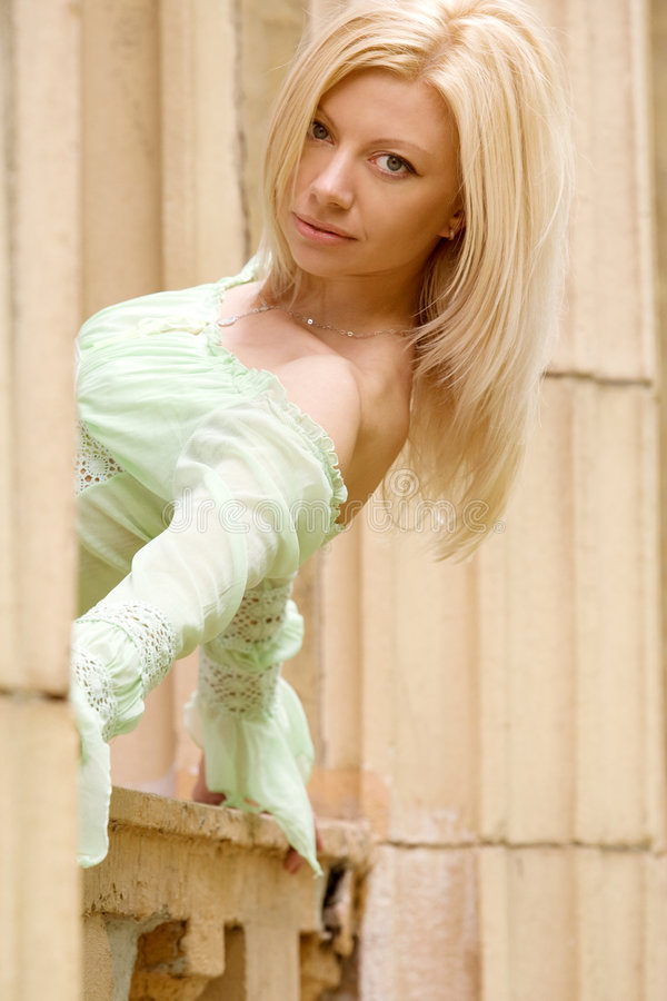 Fashionable girl standing near roman-style column royalty free stock images
