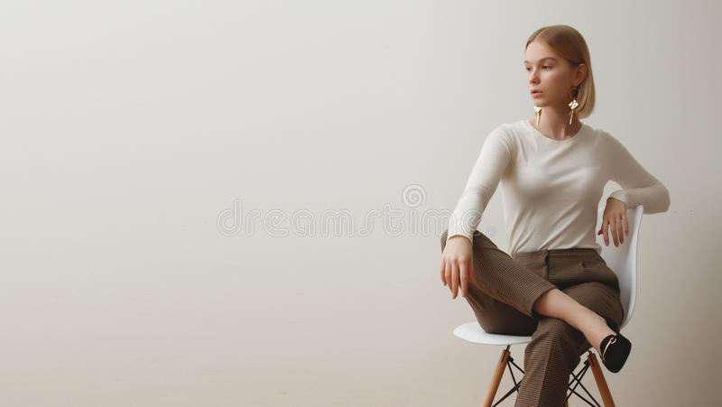 Fashionable girl in a white sweater and checkered pants . Natural lifestyle portrait of girl , emotional and fashion. Mood ,chic clothes and summer theme . Soft stock photography