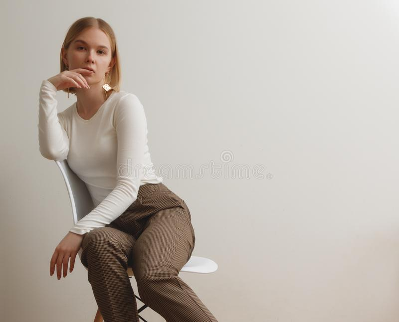 Fashionable girl in a white sweater and checkered pants . Natural lifestyle portrait of girl , emotional and fashion. Mood ,chic clothes and summer theme . Soft stock image
