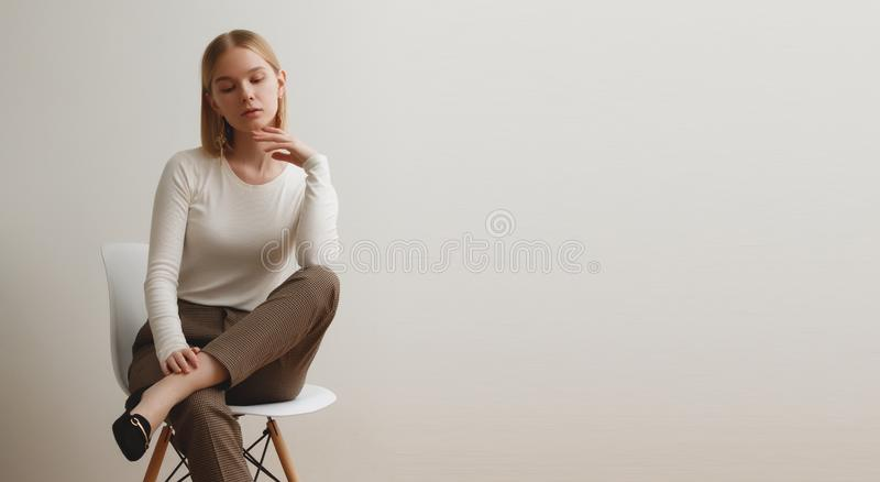 Fashionable girl in a white sweater and checkered pants . Natural lifestyle portrait of girl , emotional and fashion. Mood ,chic clothes and summer theme . Soft stock images