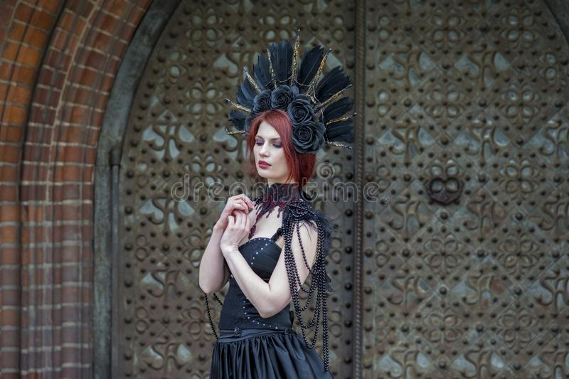 Fashionable Gothic Woman in Long Black Dress. Wearing Artistic Feather Crown. Posing Against Old Castle Gates. Horizontal Shot royalty free stock photography