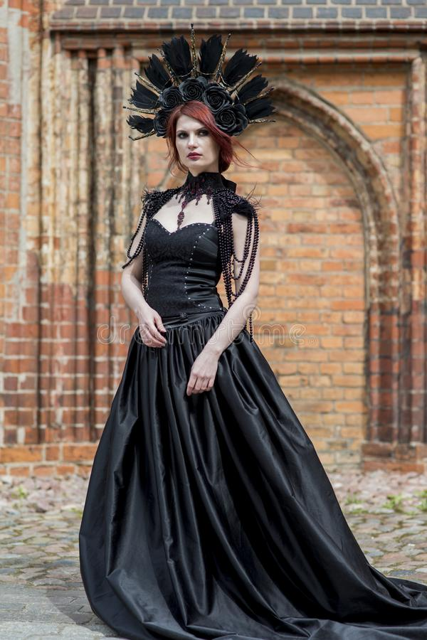Fashionable Gothic Woman in Long Black Dress. Wearing Artistic Feather Crown. Posing Against Old Castle Gates. Vertical Image stock photography