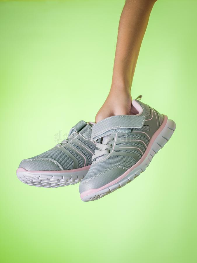 Fashionable gray sneakers in childrens hands on a green background. Color trend. royalty free stock photos