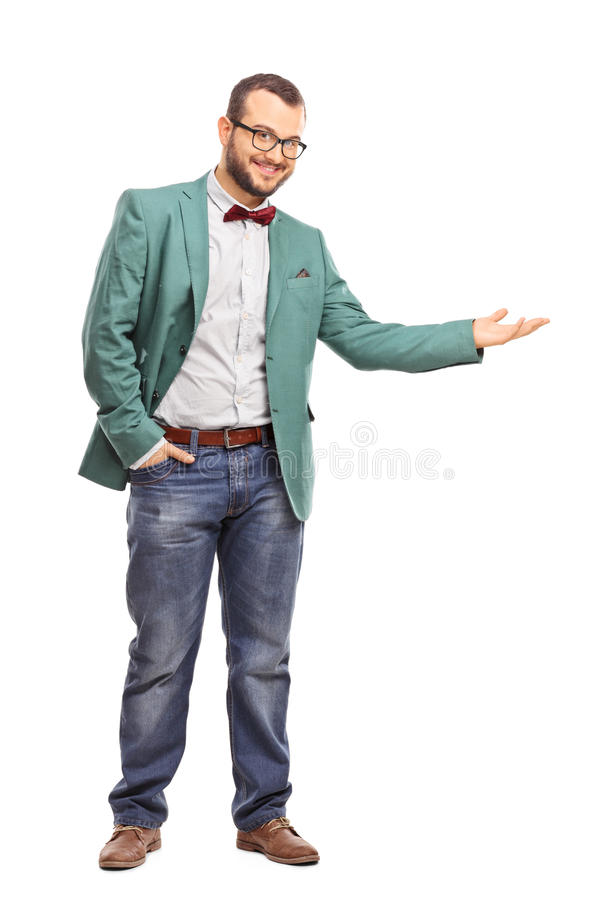 Fashionable guy gesturing with his hand. Full length portrait of a fashionable guy gesturing with his hand and looking at the camera isolated on white background royalty free stock photo