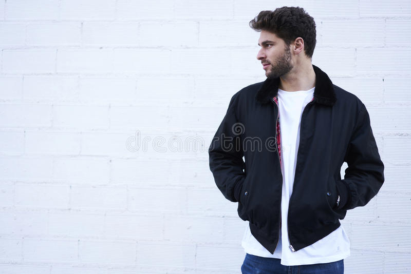 Fashionable guy in light jeans, a white T-shirt and a dark jacket royalty free stock photo