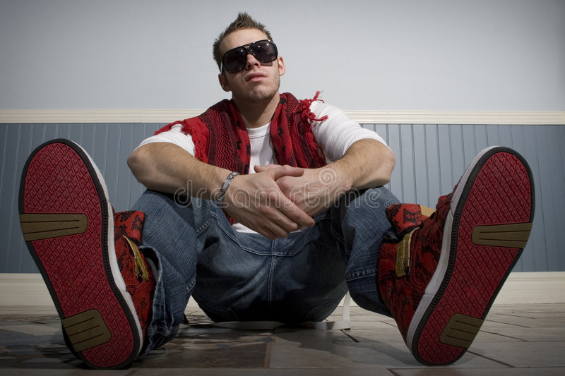 Fashionable guy sitting down looking cool stock photography