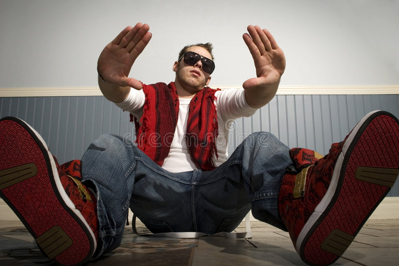 Fashionable guy sitting down looking cool stock photos