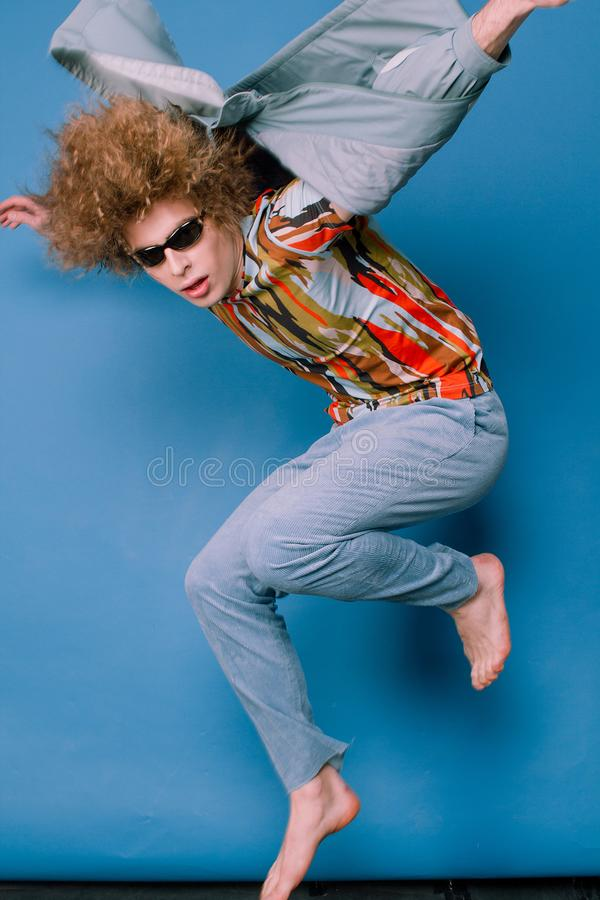 Fashionable guy in stylish clothes from the 90s. Emotionally posing in the studio stock photography