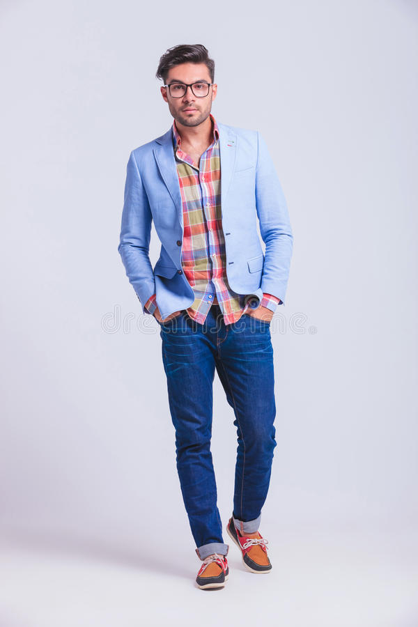 Fashionable guy wearing glasses walking in studio. Young fashionable guy wearing glasses walking in studio background whit hands in pockets while looking at the royalty free stock photos