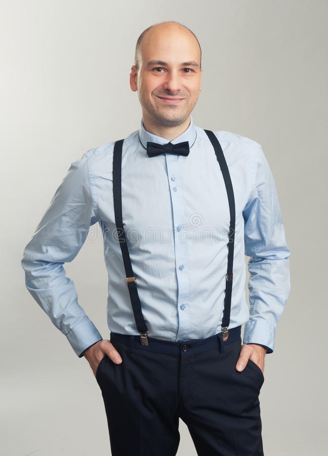 Fashionable handsome bald man in suspenders and butterfly tie royalty free stock photos