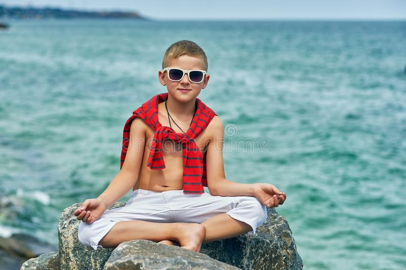 Fashionable handsome boy on the sea coast . royalty free stock image