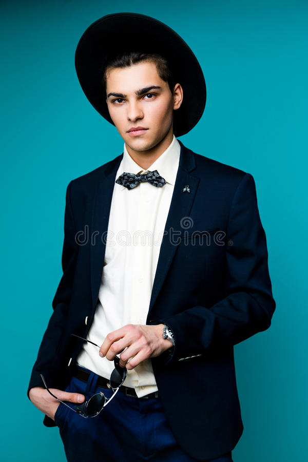 Fashionable Handsome Man in hat wearing elegant suit. royalty free stock images