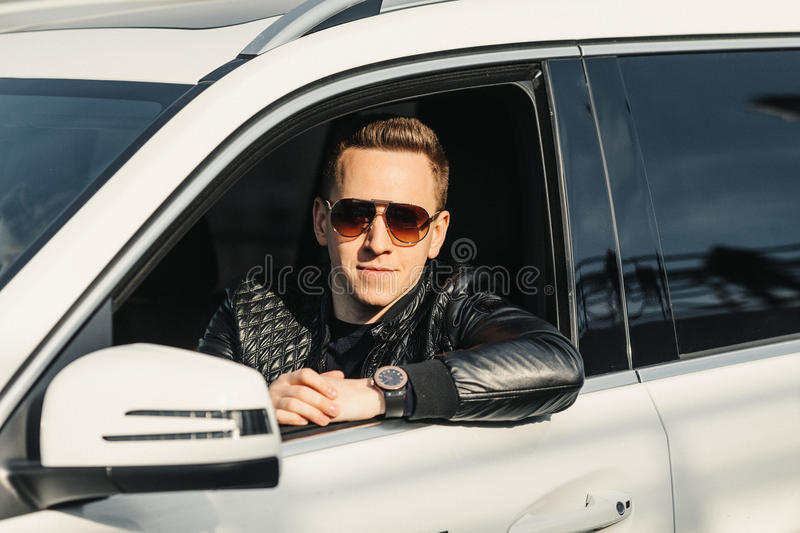 Fashionable Handsome Man in Sunglasses Sitting in his Luxury on royalty free stock photography