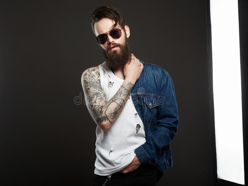 Hipster bearded Stylish boy in jeans and glasses. Fashionable handsome man with tattoo and sunglasses. Hipster bearded Stylish boy in jeans and glasses stock photography