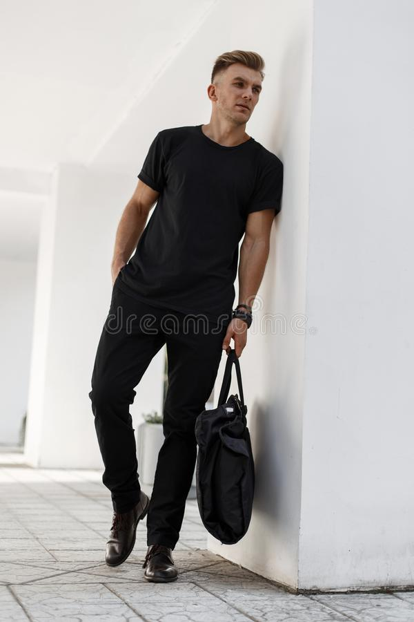 Fashionable handsome young man in black stylish clothes with royalty free stock image