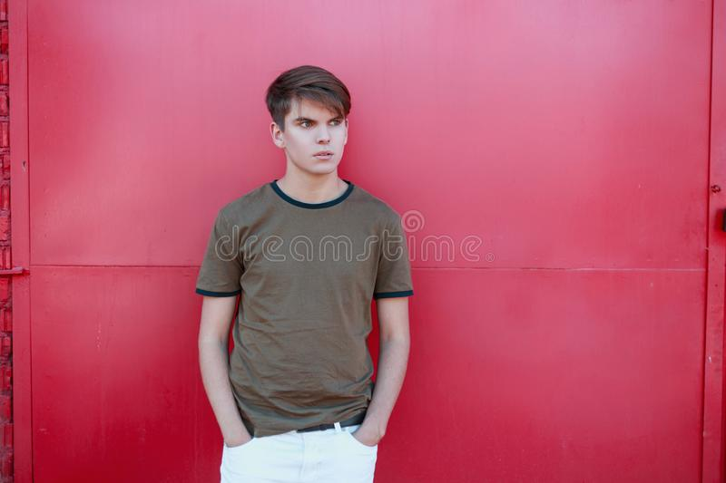 Fashionable handsome young man with a stylish hairstyle in a vintage green t-shirt in white trousers near the pink metal wall. On a warm summer day. Cool stock photos